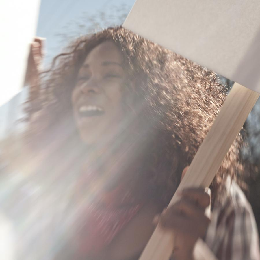 woman-in-sunshine-holding-protest-sign